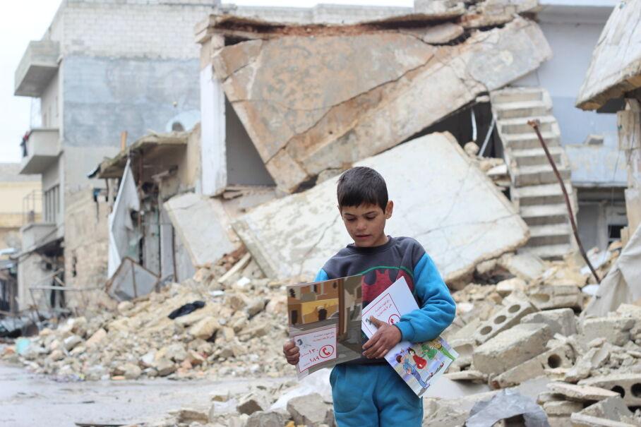 16 stycznia 2017, Syria. Dziecko z podręcznikami rozdawanymi przez wolontariuszy UNICEF