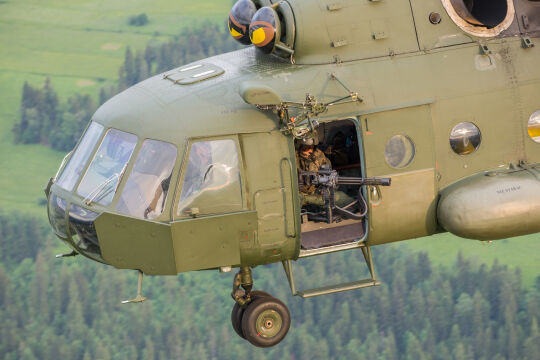 """Jeden z najnowszych Mi-17. Widać dodatkowe płyty opancerzenia na dziobie. W drzwiach strzelec z karabinem napędowym, popularnie nazywanym """"minigunem"""". To bardzo rzadki widok w polskim wojsku"""